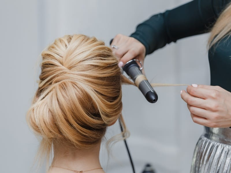 closeup of professional hairdresser hands doing beauty hairstyle a-la french twist